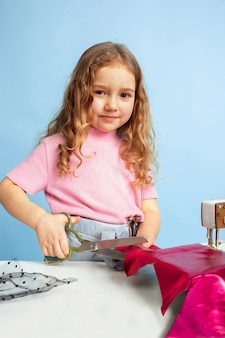Маленькая девочка мечтает о будущей профессии швеи