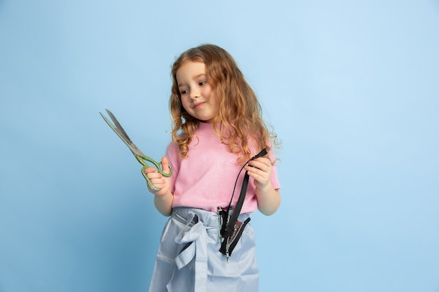 Little girl dreaming about future profession of seamstress