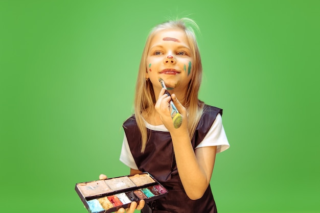 Little girl dreaming about profession of makeup artist