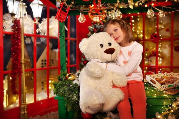 크리스마스에 기적을 꿈꾸는 어린 소녀 사랑스러운 아이 포옹 장난감 테디 베어 크리스마스 장식