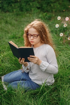 Little girl dreaming or reading a book in outdoors. education concept.