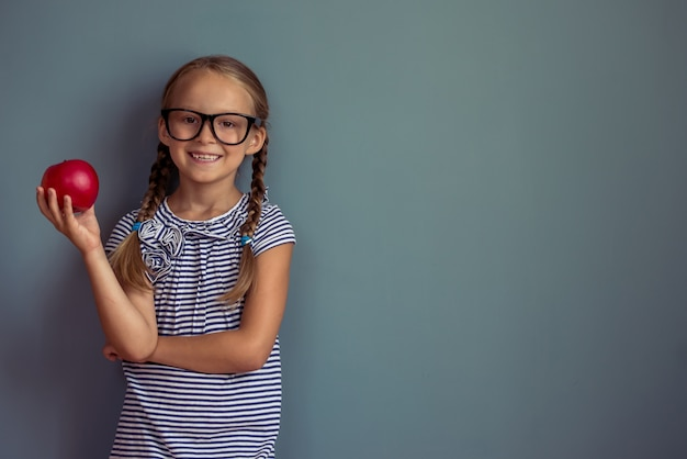Little girl in dress and eyeglasses is holding a red apple.
