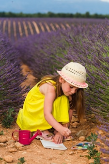 A little girl in dress and hat sits on squatting in a lavender field between the flowers. valensole, france