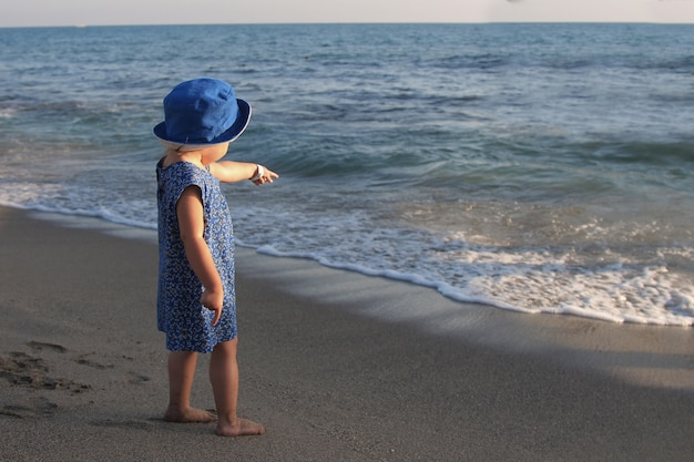 A little girl in a dress and hat walking on a sandy beach