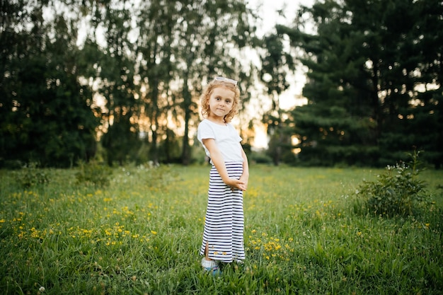 Little girl in dress shows outdoors