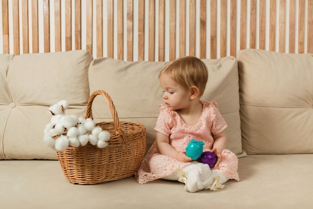 Little girl in a dress sits on a beige sofa with a basket and colorful eggs
