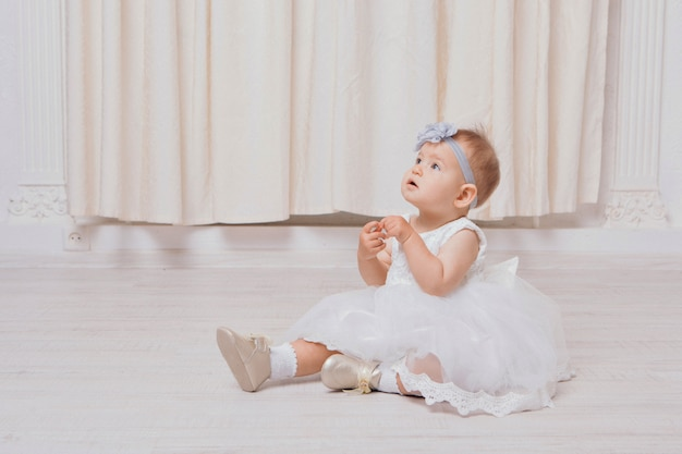 A little girl in a dress sits on the floor on a white background. child promotes children's clothes