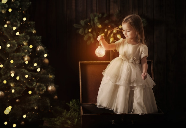 Little girl in dress with christmas tree in retro style