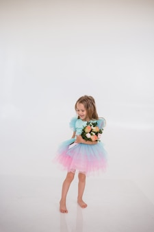 A little girl in a dress with a tutu skirt holds a bouquet of fresh flowers on a white background with a place for text
