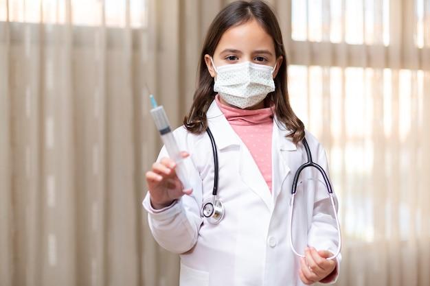 医者に扮した少女と注射器を手に持った医療用マスク