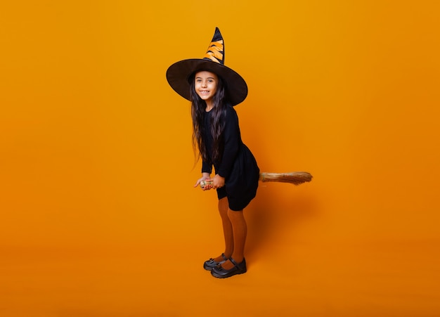 Little girl dressed as a halloween witch in a black dress and hat flies on a broomstick on a yellow background.