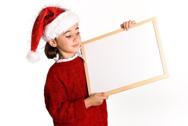 Маленькая девочка, одетые как санта-клаус, проведение белая доска