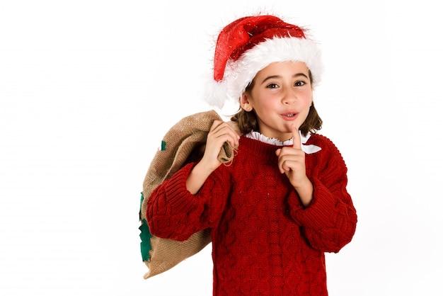 Bambina vestita da babbo natale ridere e chiede il silenzio con un sacco marrone