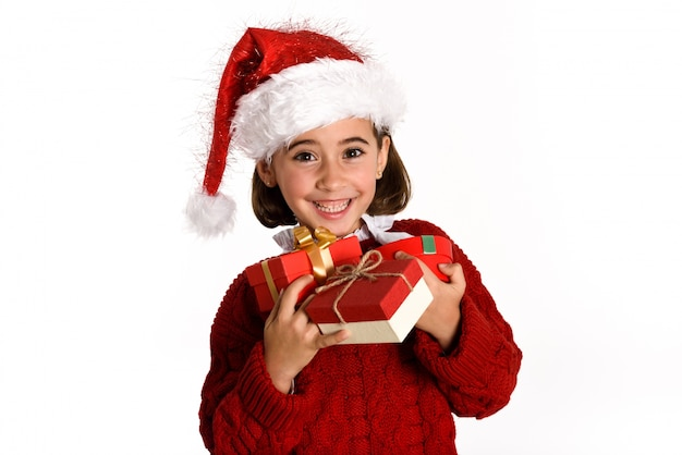 Little girl dressed as santa claus with a gift in her hands