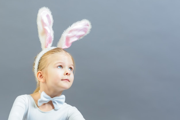 A little girl dressed as a white rabbit looks up in surprise. copy space.