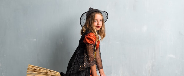 Little girl dressed as a witch for halloween holidays above on the broom and flying