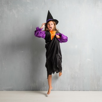Little girl dressed as a witch for halloween holidays and jumping
