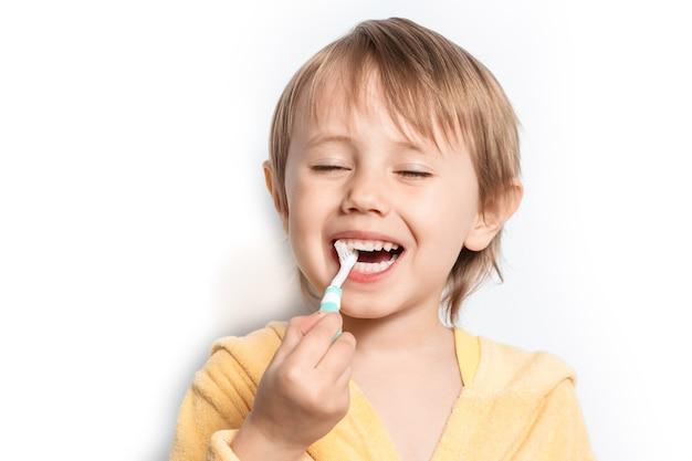 Little girl dressed in bathrobe brushing her teeth