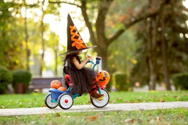 カボチャとキャンディーと自転車に乗って魔女の衣装を着た少女