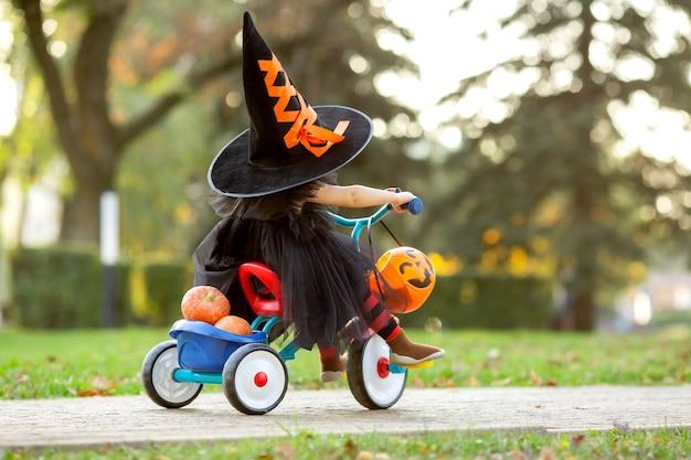 호박과 사탕으로 자전거를 타는 마녀 의상을 입은 어린 소녀