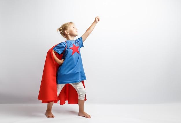 白い壁のそばに立っているスーパーヒーローのような格好の少女。