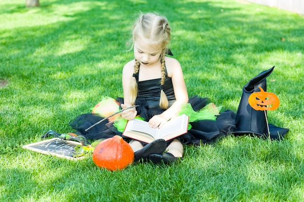 A little girl dressed in a witch costume, a black hat and black lipstick on her lips is sitting with a book and holding a magic wand. halloween.
