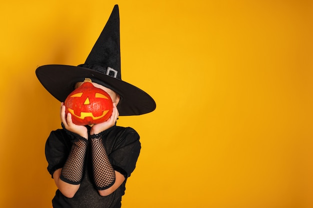 Little girl dressed in a witch costume holds a pumpkin