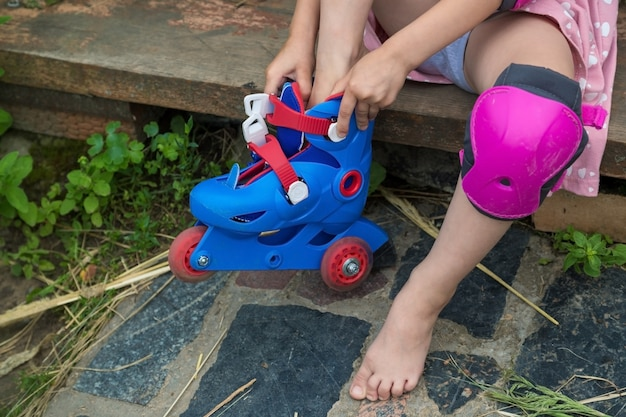 A little girl dresses roller skates sitting on the steps of her country house the concept of an active healthy lifestyle and safe riding