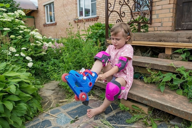 A little girl dresses roller skates sitting on the steps of her country house