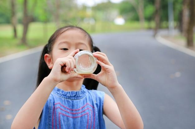 Little girl drink honeydew from glass bottle outdoors.