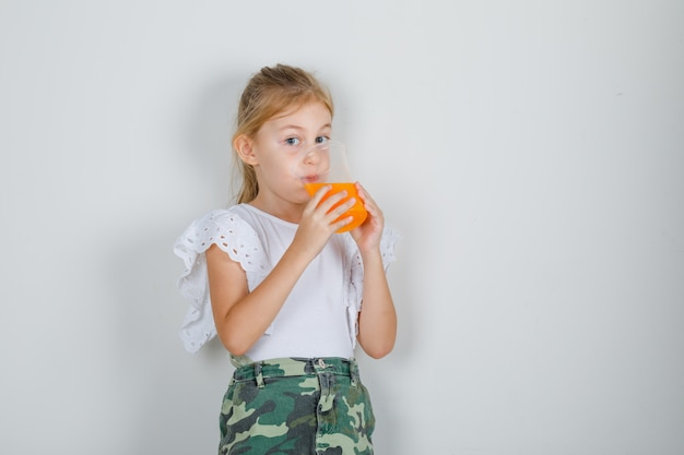 Маленькая девочка пьет фруктовый сок в белой футболке