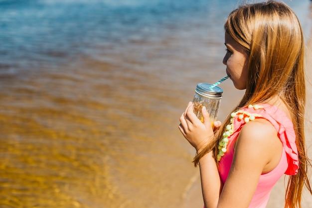 해변에 서있는 동안 주스를 마시는 어린 소녀