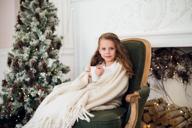 Маленькая девочка пьет молоко возле елки утром дома