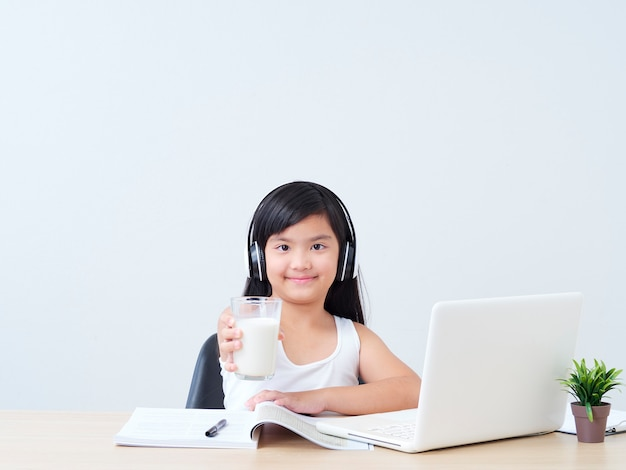 Little girl drinking milk while studying