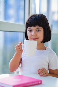 Little girl drinking tea of milk at home