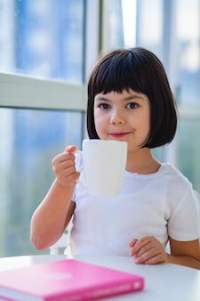 집에서 우유 차를 마시는 어린 소녀