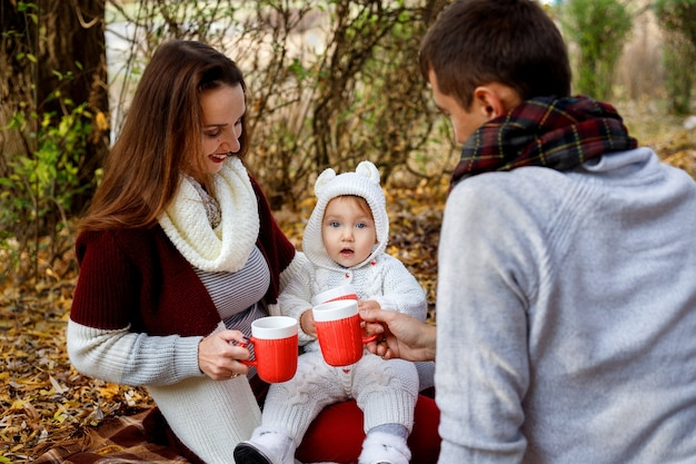Little girl drinking tea with her parents in the autumn park