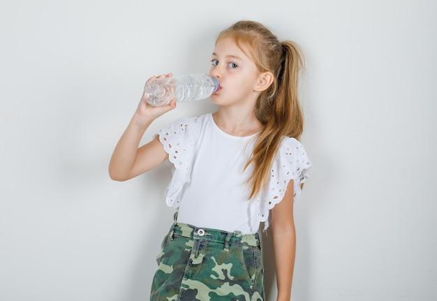 Маленькая девочка пьет воду в белой футболке, юбке и хочет пить
