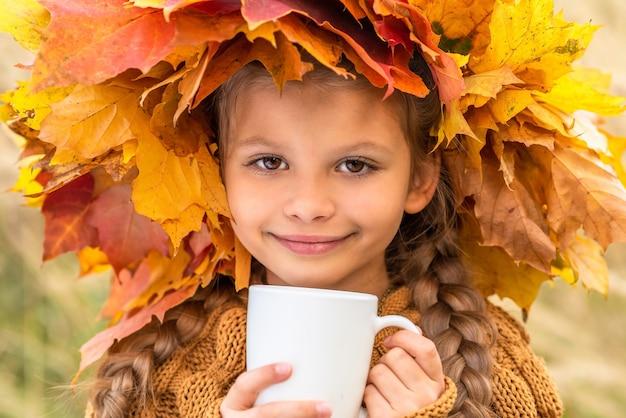 어린 소녀는 단풍 나무 잎의 가을 화환에 뜨거운 음료를 마신다
