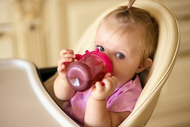 Маленькая девочка пьет компот из чашки-поильника