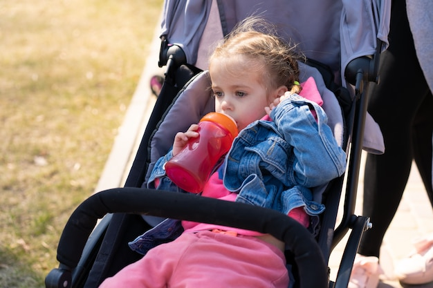 Little girl drinks juice from a bottle while sitting in a baby carriage on a walking