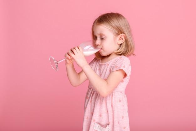 어린 소녀는 분홍색 표면에 유리에서 우유를 마신다