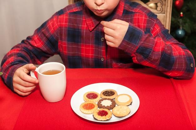 小さな女の子は、クリスマスツリーの背景にお茶とビスケットを飲みます