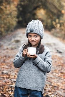 Маленькая девочка пьет чай в осеннем парке