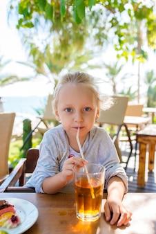 Маленькая девочка пьет сок на улице.