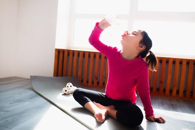 어린 소녀는 집에서 운동 후 물을 마신다. 귀여운 아이가 실내 매트에서 훈련하고 있습니다. 운동복을 입은 작은 검은 머리 여성 모델이 방 창문 근처에서 운동을 하고 있습니다.