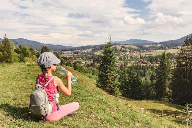 Маленькая девочка пьет воду из бутылки, сидя на траве в горах
