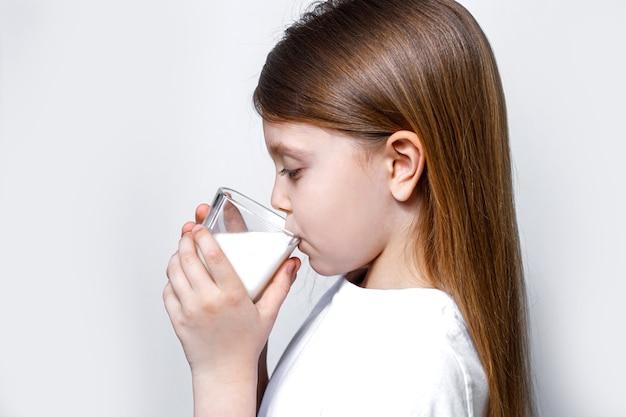 小さな女の子が透明なガラスから白い牛乳を飲む