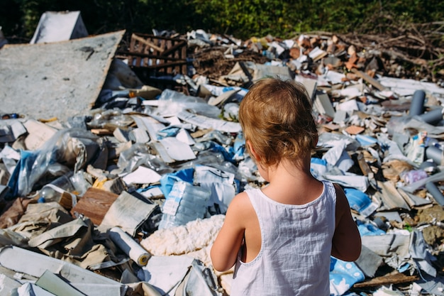 Little girl at a dump among a heap of scattered garbage in the forest