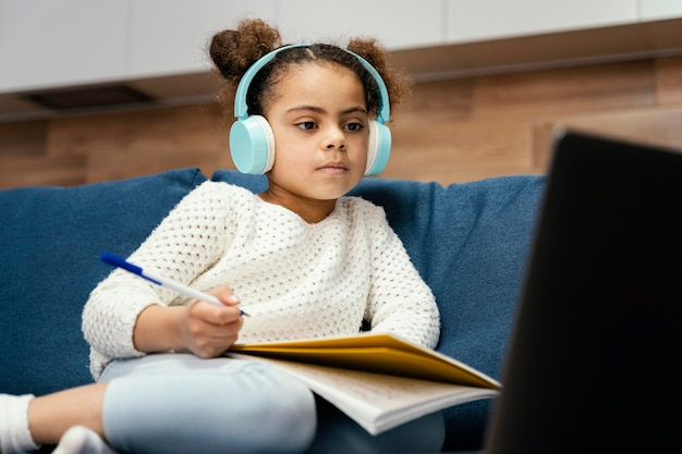 Little girl during online school with laptop and headphones